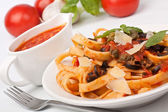 Linguine pasta with fresh tomato puttanesca sauce, cheese and ba — Stock Photo