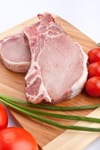 Raw pork chops with vegetables on chopping board — Stock Photo