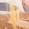 Uncooked homemade egg pasta lifted up with a knife — Stock Photo #41990117