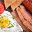 Fried egg, sausages, bacon and toast — Stock Photo