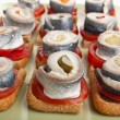 Canapes with tomatoes and norwegian herring — Stock Photo #42006371