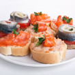 Canapes with tomatoes and norwegian herring — Stock Photo