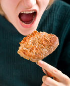 Woman taking a bite of a rump steak — Stock Photo