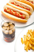Glass of cola, french fries and three  hotdogs — Stock Photo