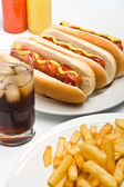 glass of cola, french fries and three classic hotdogs with must — Stock Photo