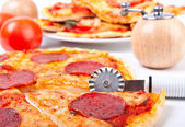 Sliced salami pizza , a pizza knife, a wooden pepper-box — Stock Photo