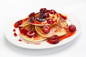 Pancakes with sweet cherry sauce — Stock Photo
