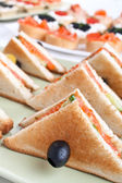 Club sandwiches with salmon and cucumbers — Stock Photo