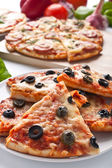 Different sliced pizzas with ingredients — Stock Photo
