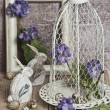 Easter eggs in a cage, spring blue flowers, quail eggs, white bunnies , white frame, white frame, wooden floor nature — Stock Photo #43889641