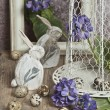 Easter eggs in a cage, spring blue flowers, quail eggs, white bunnies , white frame, white frame, wooden floor nature — Stock Photo #43889765