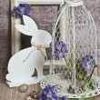Easter eggs in a cage, spring blue flowers, quail eggs, white bunnies , white frame, white frame, wooden floor nature — Stock Photo #43889865