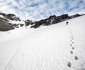 Trekker and footprints in the snow.  — Stock Photo