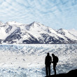 Silhouette of a couple admiring beautiful view of glacier and mo — Stock Photo