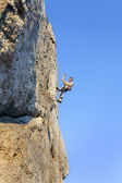 Extreme rock climbing, man on natural wall with blue sky. — Foto de Stock