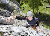 Happy woman climbing rock, active holidays. — Стоковое фото