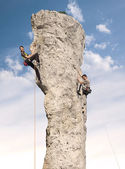 Climbers in action, young woman and man climbing difficult rock. — Stock Photo