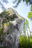 Young woman climbing difficult rock in forest. — Stock Photo