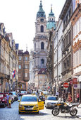 Street of Prague crowded with tourists and vehicles. — Stock Photo