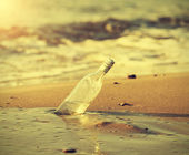 Bottle in water at sunset, retro instagram vintage effect. — Stock Photo