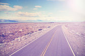 Asphalt country road with back light, vintage style — Stock Photo