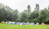 Tenten op camping site in de regen. — Stockfoto
