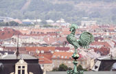 Rooster overlooking Prague roofs — Stock Photo