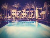 Retro vintage stylepicture of pool side of hotel at night. — Stockfoto