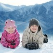 Girl and boy lie on the snow — Stock Photo