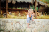 Little girl sitting on the curb — Foto de Stock