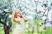 Cute little girl standing under a tree — Stock Photo
