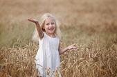Holčička chodí na poli pšenice — Stock fotografie