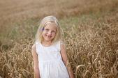 Petite fille marche sur un champ de blé — Photo