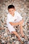 Boy sits on stone seacoastby near the sea — Stock Photo