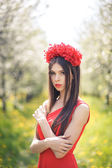 Young pretty girl posing in summer field with flowers — Стоковое фото