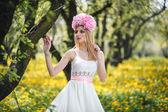 Giovane bella ragazza è in posa con fiori — Foto Stock
