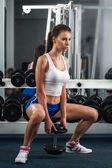 Beautiful young woman during fitness with dumbbells. — Stock Photo