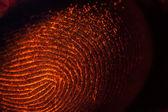 Red-orange fingerprints on black — Stockfoto