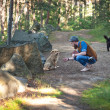 Man petting dog in the forest — Stock Photo #50071881