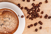 Coffee cup and saucer on a wooden table. with grains — Stockfoto