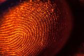 Red-orange fingerprints on black — Stock Photo