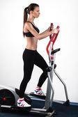 Image de la jeune formation féminine sur simulateur en gym — Photo