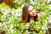 Portrait of a beautiful spring girl in tree flowers. — Stock Photo