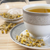 Dried camomile flowers surrounding fresh up of camomile tea — Stock Photo