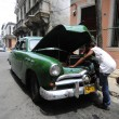 A man carefully repair his old American car on street — Stock Photo