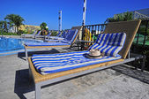 View of striped long deck chairs set by swimming-pool — Стоковое фото