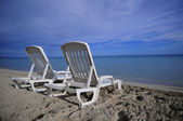 Empty tropical beach chairs on sand at shoreline in the Caribbea — Stock Photo