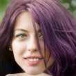 Purple haired girl with a green leafed background — Stock Photo #42316451
