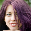 Purple haired girl with a green leafed background — Stock Photo