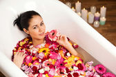 Young woman lying in the bath of rose petals — Stock Photo